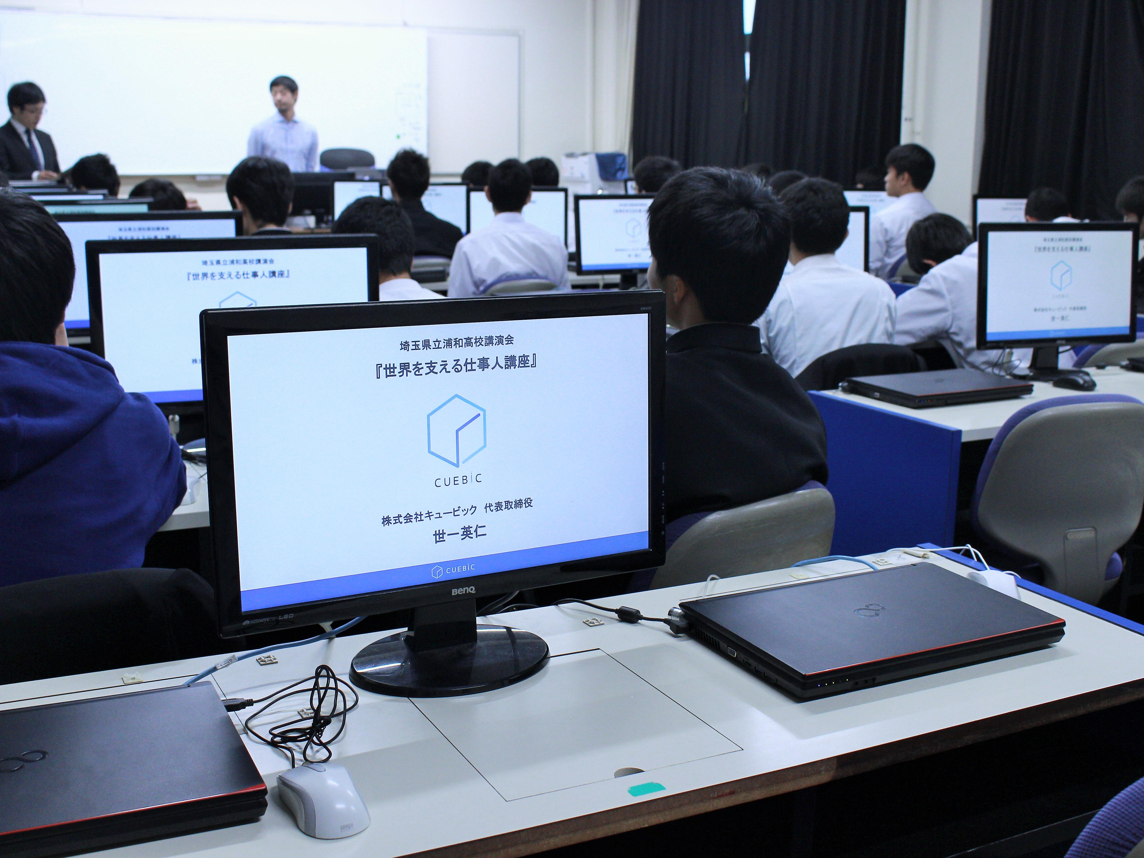 会場となった視聴覚室には、世一の作成したスライドが表示されています